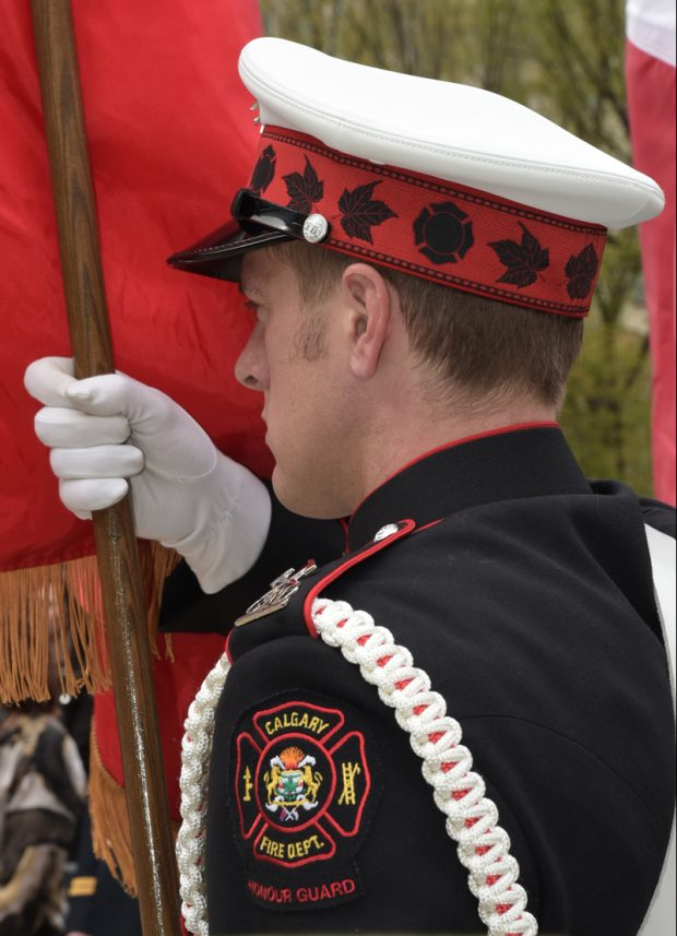 Close up of flag bearer from left shoulder patch to white cap, in ¾ profile, showing white gloved right hand holding flag pole upright.