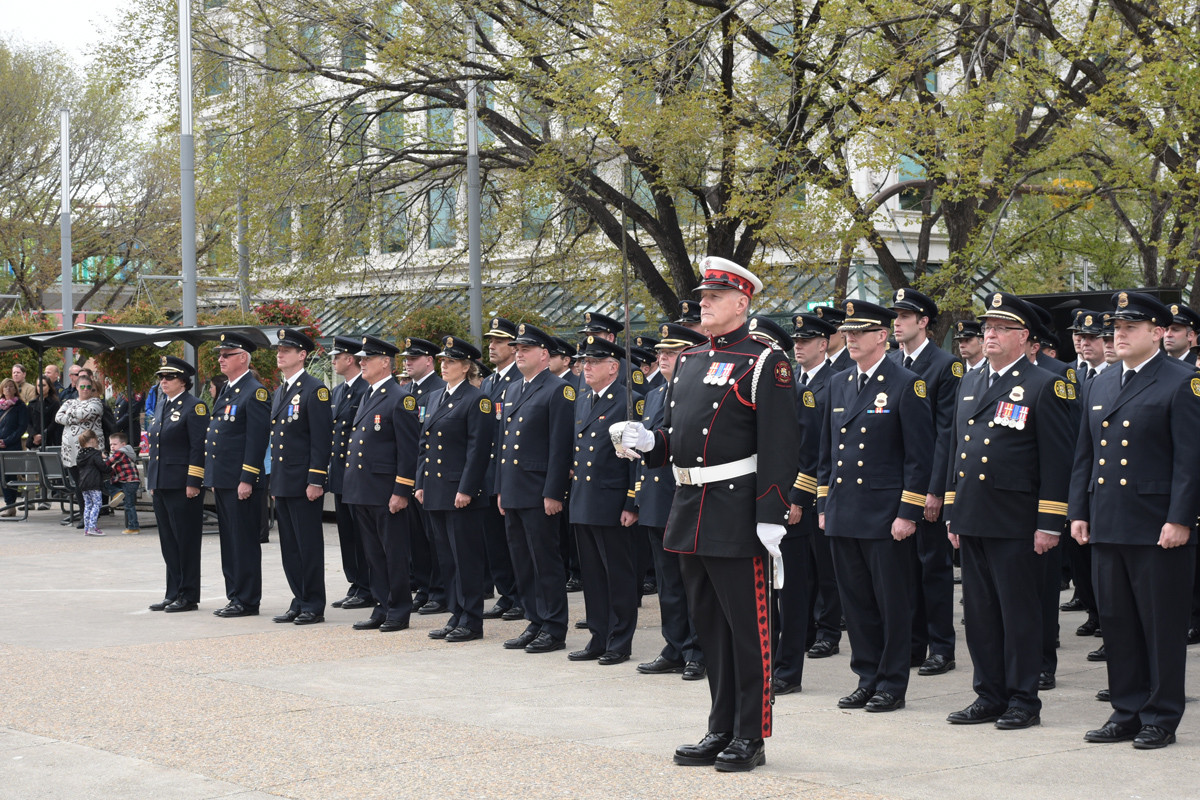 Guardsman Blaine Gray stands with ceremonial sword in front of row of uniformed firefighters at Tribute Plaza in 2015.