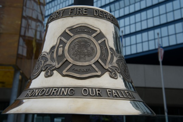 Close up on silver bell inscribed Calgary Fire Department and Honouring Our Fallen with CFD crest. City hall can be seen in the background.