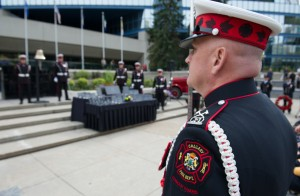 Uniformed Commander is seen in 3/4 profile from behind, from waist up, in full uniform. In background is Tribute Plaza and City Hall.
