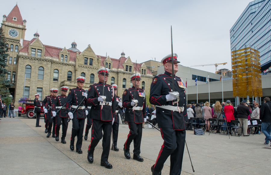 Honour Guard marches in full dress uniform at Tribute Plaza in front of old city hall, holding ceremonial swords and axes.