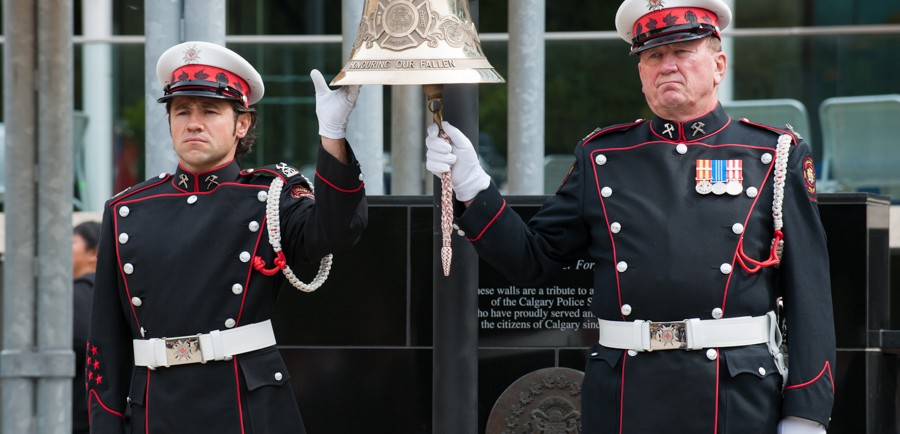A large, hanging bell is held and rung by two Honour Guards in full dress uniform and white gloves, in front of the memorial at Tribute Plaza, City Hall