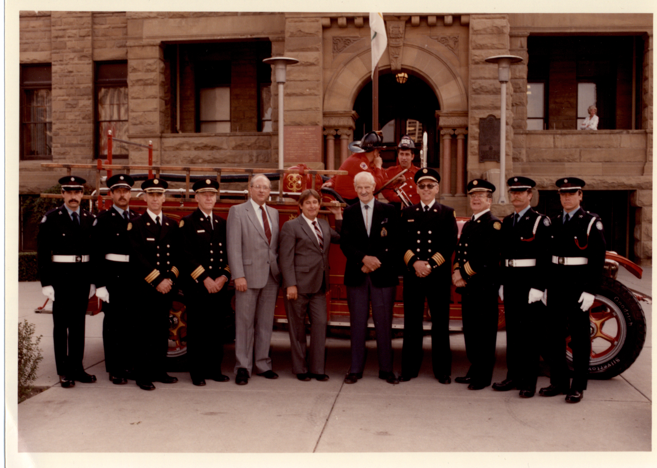 Eight guard members stand with former mayors, in suits, in front of antique fire truck and sandstone city hall.