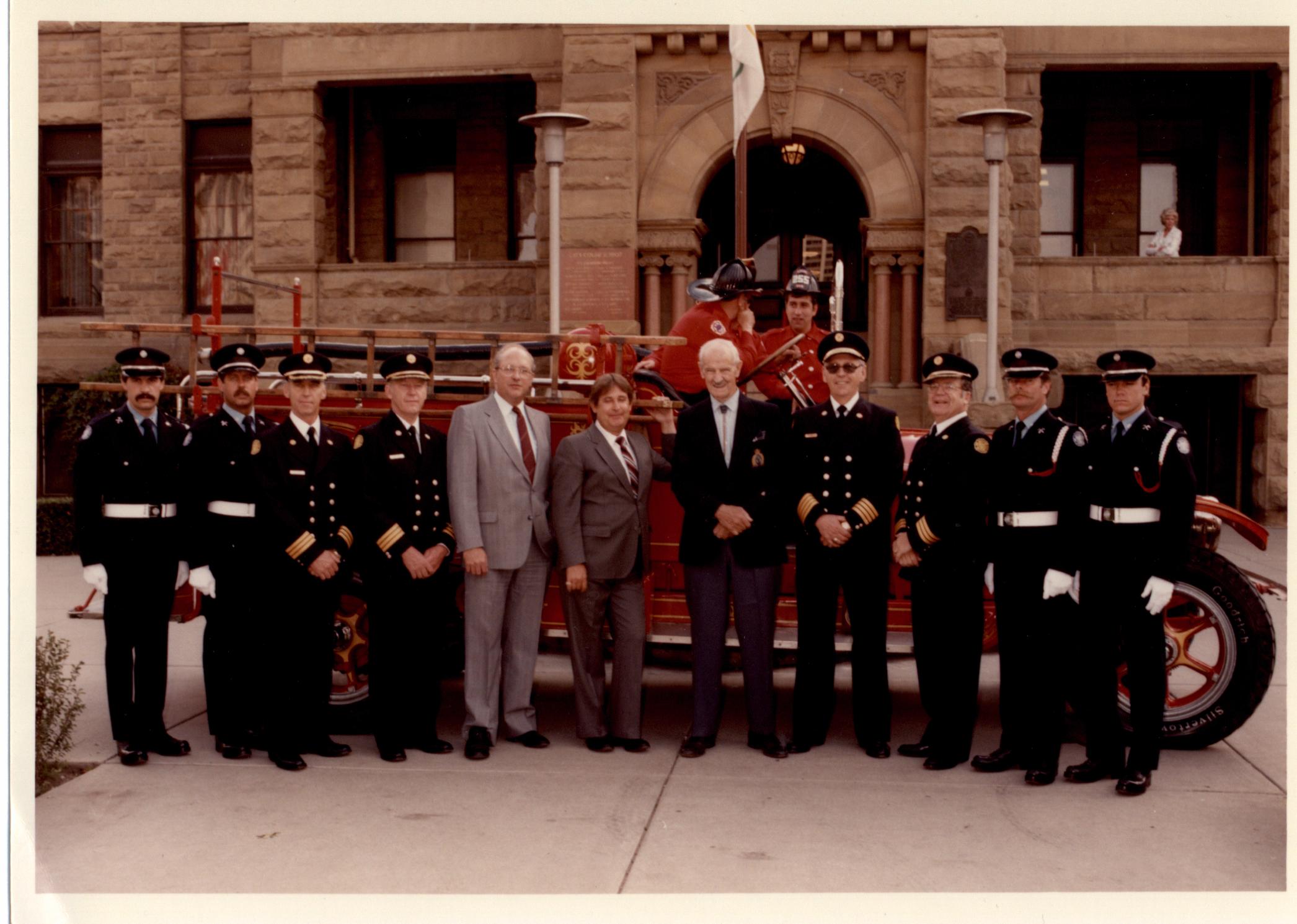Huit membres de la garde d'honneur avec d'anciens maires, en habit, devant un camion de pompier d'époque et l'hôtel de ville en grès