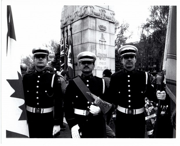 Three Honour Guard bearing flags and a ceremonial axe stand in front of the WWI Memorial at Central Memorial Park. Photo is black and white.