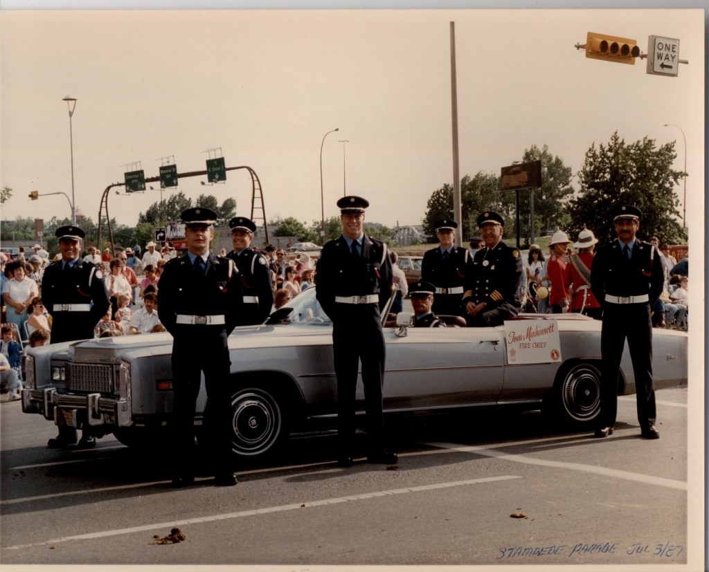 Six Honour Guard members are standing around a convertible with sitting Fire Chief. In the background are parade goers lining the street.
