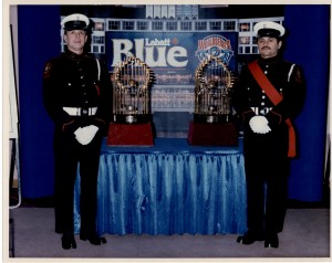 Guard Members Rick Choppe and Shannon Pennington stand with the 1993 World Series baseball trophies, both in full dress. The trophies are displayed on a table draped in a blue cloth, with blue background.