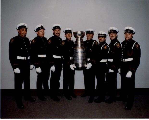 Eight firefighters in uniform stand either side of the Stanley Cup, being held up in centre.