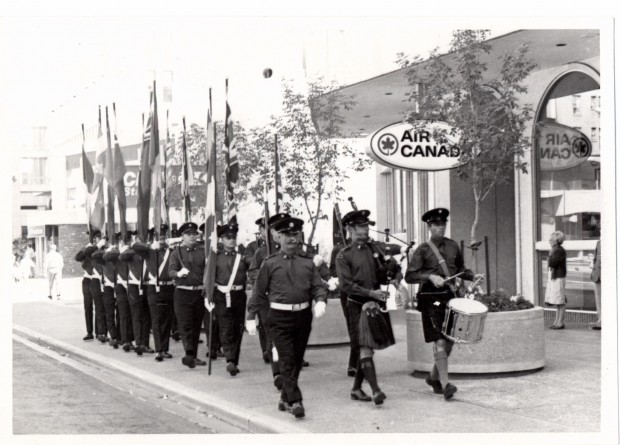 Honour Guard parades past palliser square in black and white photo, most bearing flags, and led by pipes and drums.