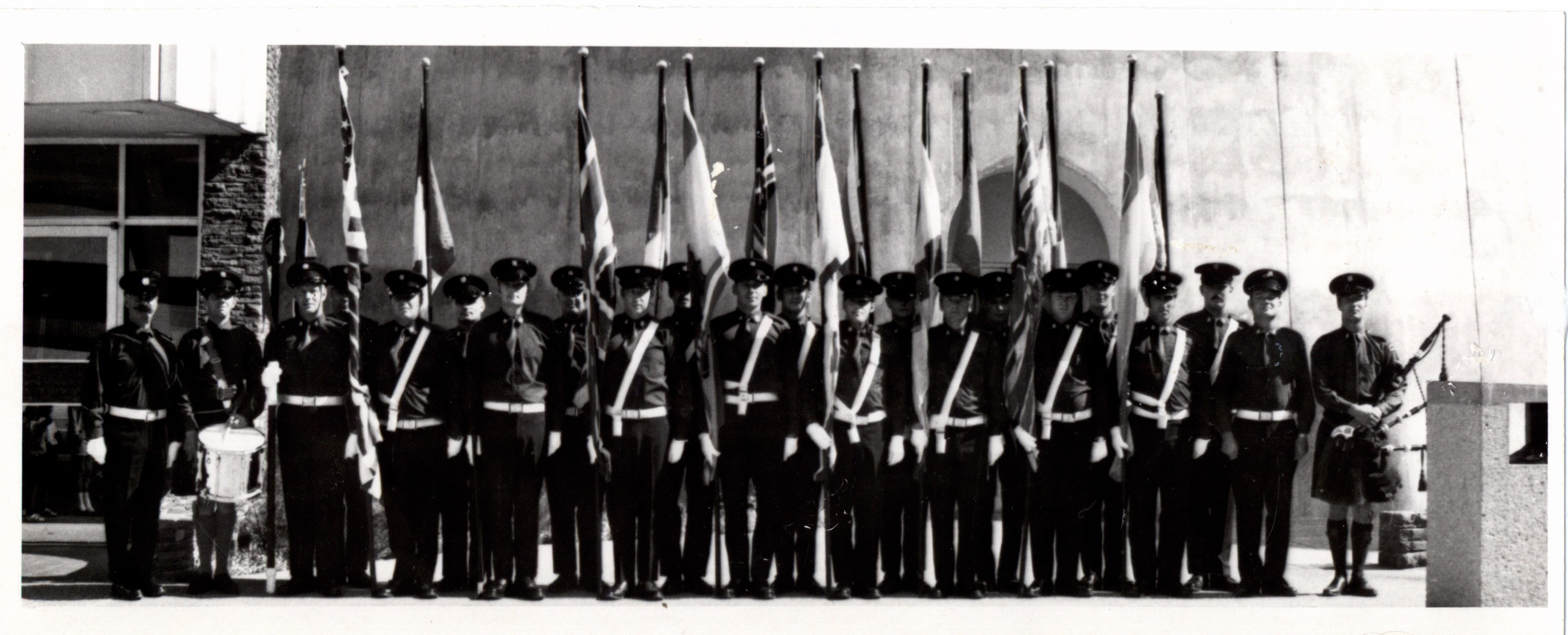 Black and white photo showing more than 20 men standing in a line at attention in full uniform at the base of the tower. Most carry flags. Men at either end are carrying pipes and drums