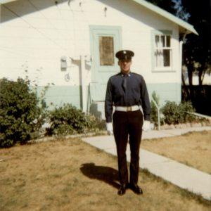 Dennis McIvor, sur le parterre d'une maison blanche et bleue portant l'uniforme original numéro un de la garde d'honneur, avec cravate rentrée dans sa chemise