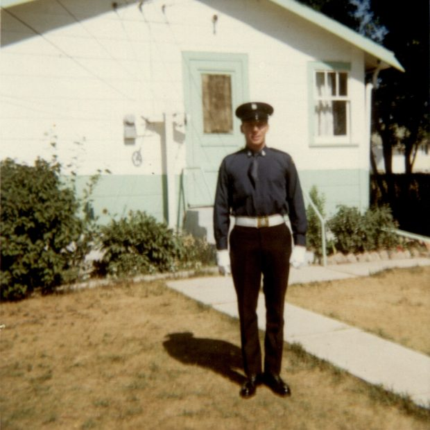 Dennis McIvor, standing on lawn in front of white and blue house, dressed for Honour Guard duty, in original Number 1 dress with tie tucked in.