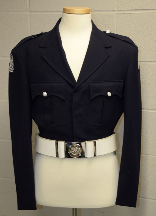 Original, Number 1 dress Honour Guard uniform. Black battle style jacket with CFD patch on both shoulders, two breast pockets, box pleated, with scalloped flaps and two epaulettes secured by silver buttons. White leather belt and silver plated buckle over the jacket on a white headless mannequin.