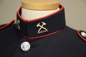Close up of collar pins, with crossed axes and the previous spelling of 'Honor Guard'.
