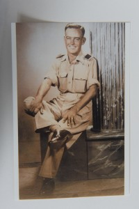 A sepia toned photo shows a man in military uniform, sitting causally with right leg crossed over left knee, shirt sleeves rolled up, and both hands on knees.