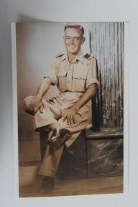 Sur cette photo sépia, on aperçoit un homme en uniforme militaire, assis de manière décontractée, la jambe droite sur le genou gauche, les manches de chemise retroussées, les deux mains sur les genoux.