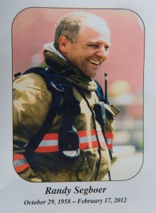 Memorial photo card showing a smiling firefighter in firefighting gear. Underneath the photo is: 'Randy Segboer October 29, 1958 - February 17, 2012'