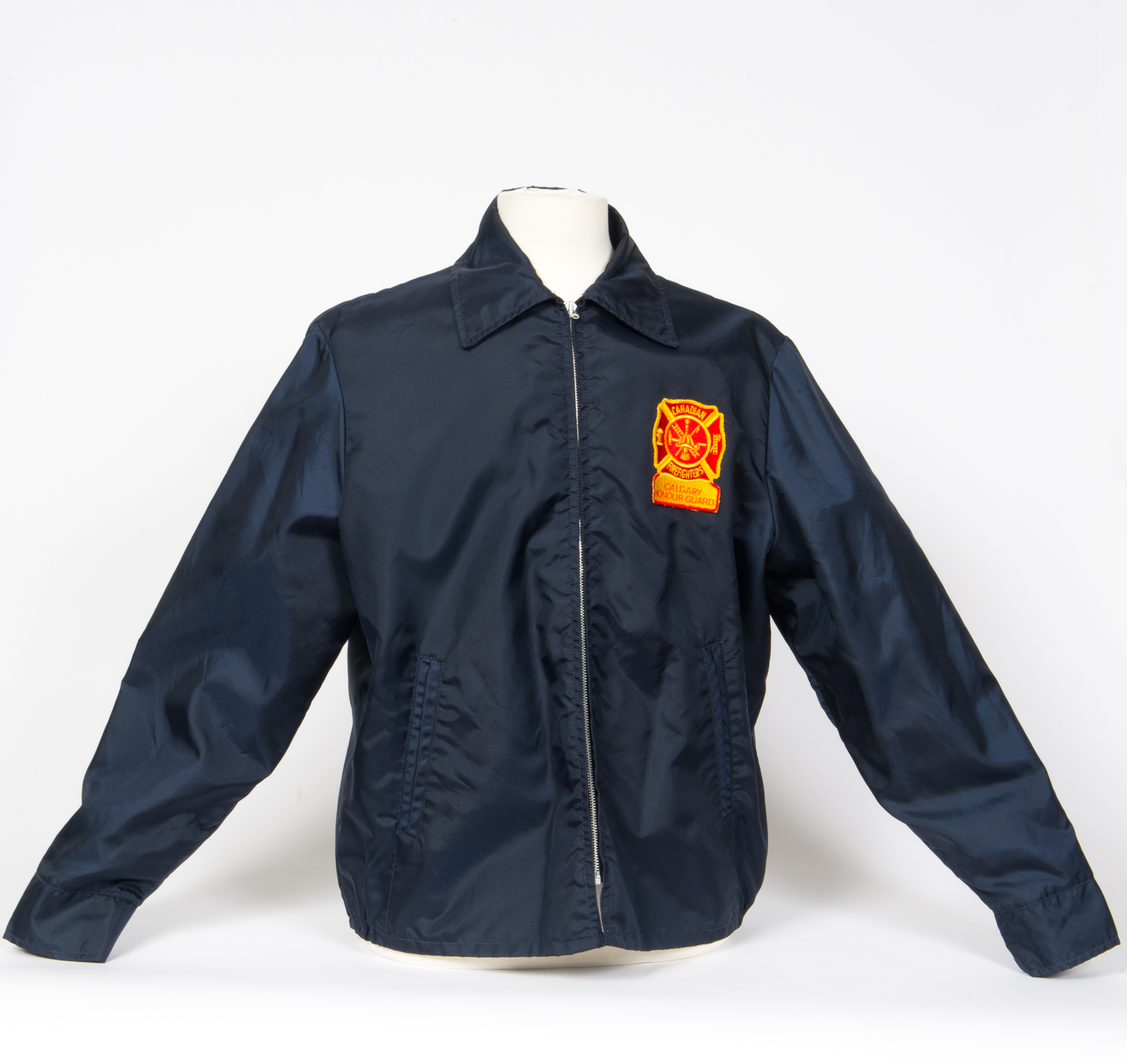 Navy zip up weatherproof raincoat with collar, with yellow and red Firefighters Calgary Honour Guard patch.