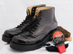 Bottes noires lacées de la garde d'honneur avec cire de marque Kiwi dans un contenant rond et brosse rouge
