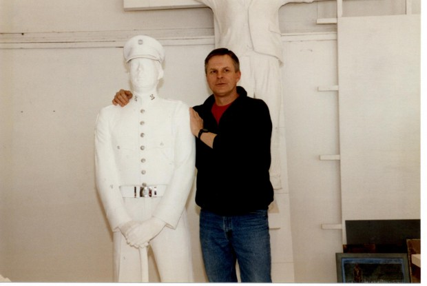 Member Rick Choppe, in casual clothes, stands next to his life size white plaster cast, in uniform, for the honour guard statue.