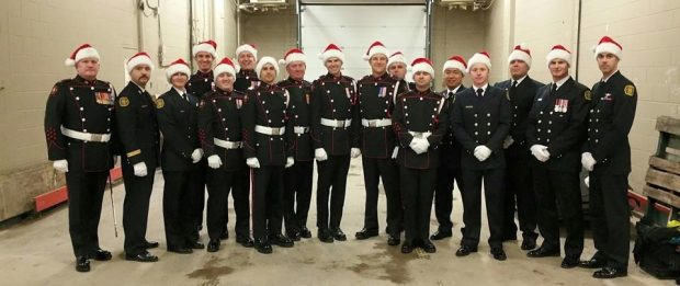 Seventeen firefighters in dress uniform all stand in a line, smiling backstage, wearing red Santa hats