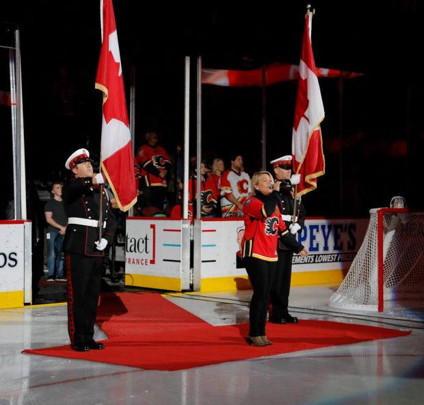 Two Honour Guard members stand at attention in full dress each carrying the Canadian Flag while blonde singer sings the National Anthem in a Calgary Flames jersey.