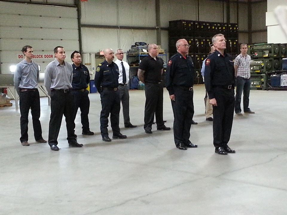 14 men stand at attention during a drill to try out for Honour Guard.