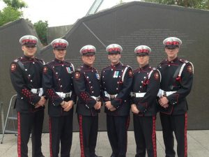 Six Honour Guard members stand with hands together in front of the engraved memorial in Ottawa.