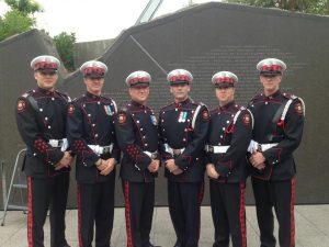 Six membres de la garde d'honneur les mains jointes, devant le monument commémoratif, à Ottawa