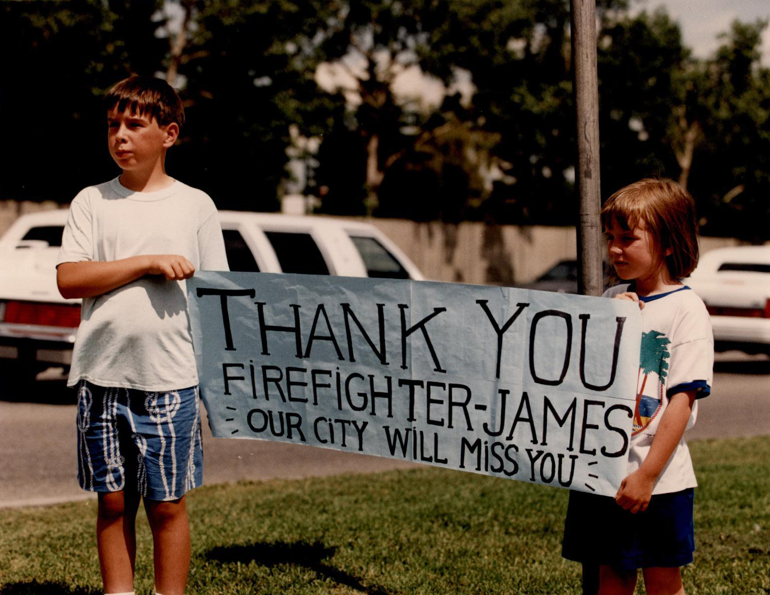 Along the route of the procession two children hold up a banner: 'Thank You Firefighter James. Our City will miss you.'