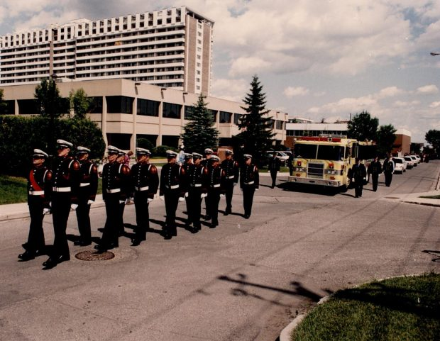 Several Honour Guard members march in full dress, leading a yellow fire engine at the front of Morley James' funeral procession.
