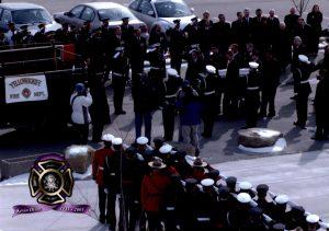 Des membres de la garde d'honneur embarquent le cercueil de Kevin Olson, pompier de Yellowknife, sur l'autopompe cérémoniale. Des pompiers et des polices montées sont au garde-à-vous et gardent le salut.