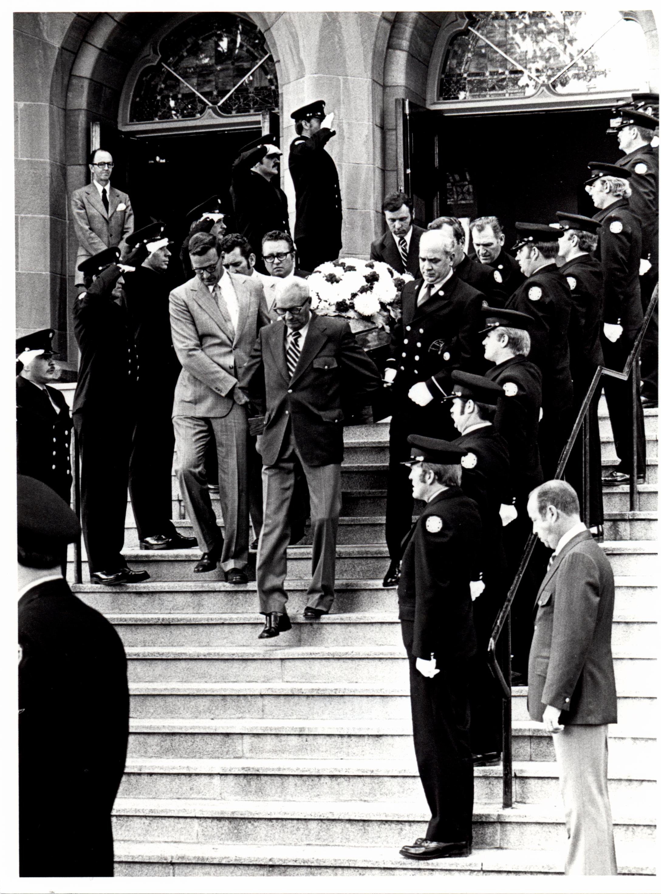A funeral cask held by pallbearers leaves a church; the path is lined by uniformed and saluting firefighters.