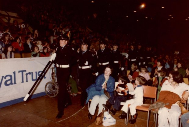 Honour Guard marching through the crowd seated on bleachers and on floor seats at a community parade.