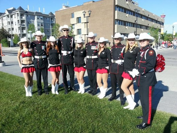 Five uniformed Guard members are pictured with five Stampeders' Outriders in their cheerleading uniforms and white hats
