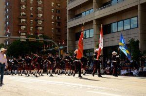 La garde d'honneur défile au centre-ville avec les drapeaux du service d'incendie, du pays et de l'union au Stampede de 2015. Elle est suivie des membres des Pipes and Drums en jupe écossaise rouge.