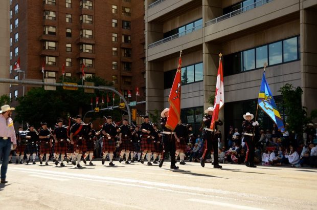 Honour Guard parades through downtown with departmental, national and union flags at 2015 Stampede, followed by the red kilted Pipes and Drums.