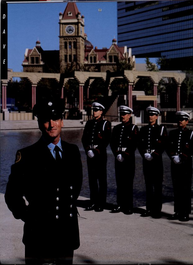 A firefighter stands in the left foreground, with four Honour Guard members standing at attention mid ground. In the background is Olympic Plaza and historic sandstone city hall.