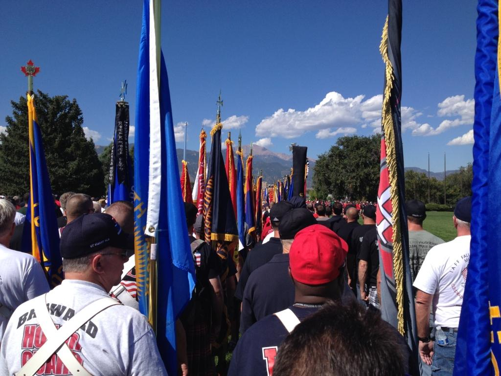 Honour Guards in casual dress prepare to march in memorial procession, with backs to camera, holding colourful flags. In the background are mountains.