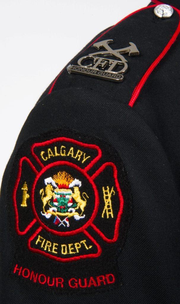 Gros plan de l'épaule droite de la veste de la garde d'honneur avec insigne et logo du service d'incendie de Calgary et épinglette argentée aux haches croisées de la garde d'honneur
