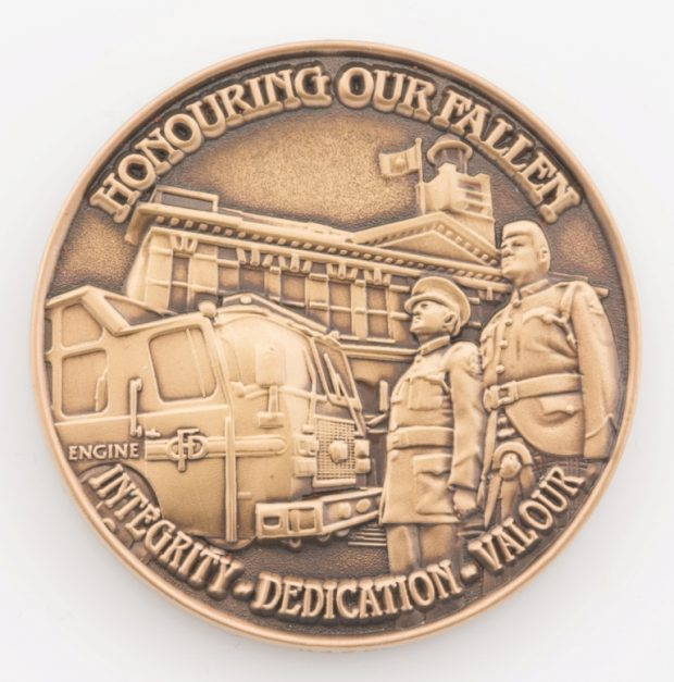 Front side of CFD challenge coin. Inscribed 'Honouring Our Fallen. Integrity, dedication, valour' and showing two firefighters standing with fire engine and fire hall in the background