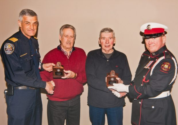 Founders Brian Freney and Dennis Mcivor, in casual outfits, are presented with their commemorative plaques by two uniformed firefighters.