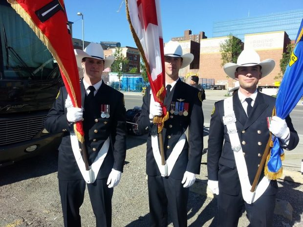 Three smiling Honour Guards in uniform with medals, wearing white cowboy hats and holding flags, prepare to march in the parade. It's a sunny day with city buildings in the background.