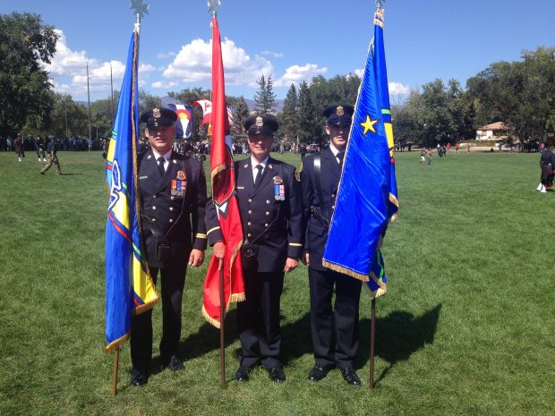 Three Honour Guard members stand in full uniform in a green, grassy field, each holding a different flag.