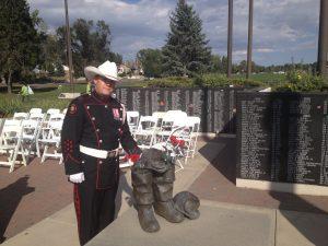 Un garde d'honneur du service d'incendie de Calgary en uniforme et chapeau de cowboy blanc à côté de la sculpture d'une paire de bottes, devant le mur commémoratif portant le nom des pompiers disparus