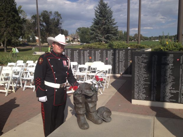 A CFD Honour Guard in unifrom with white belt, gloves and cowboy hat stands with a sculpture of boots, in front of a memorial wall inscribed with names.