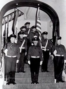 Black and white photo of eight members of the Honour Guard stand at attention on a set of stairs underneath an arch at their first engagement in 1971.