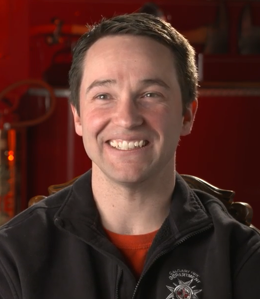 Head and shoulder colour photograph of Tobias Breuer wearing a black jacket with a Calgary Fire department logo.