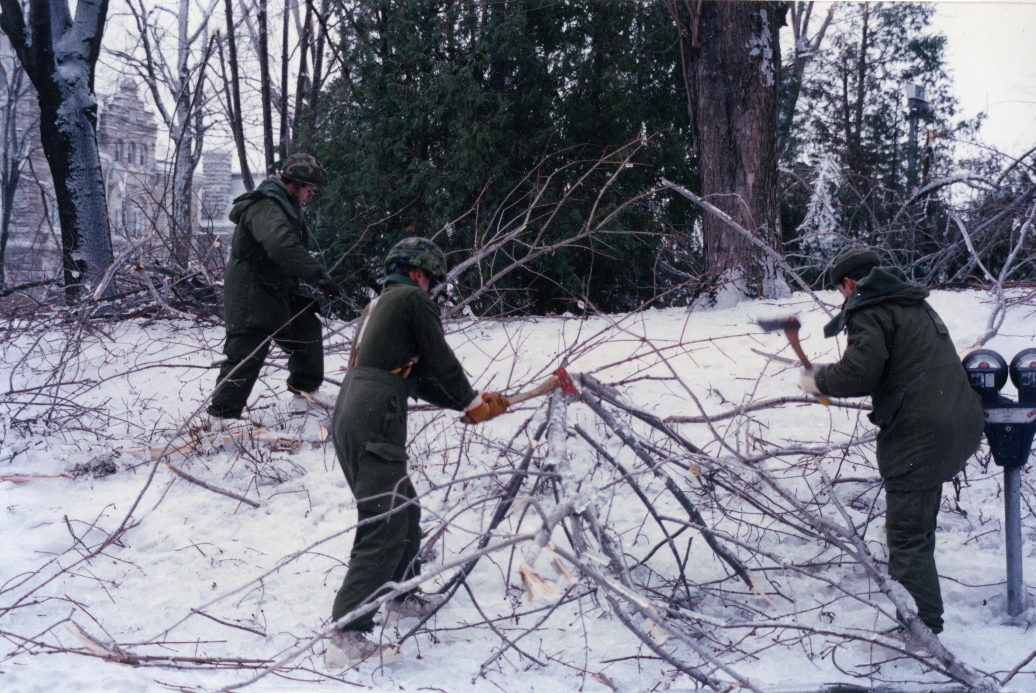 Les militaires brisent les branches à la hache pour les ramasser.