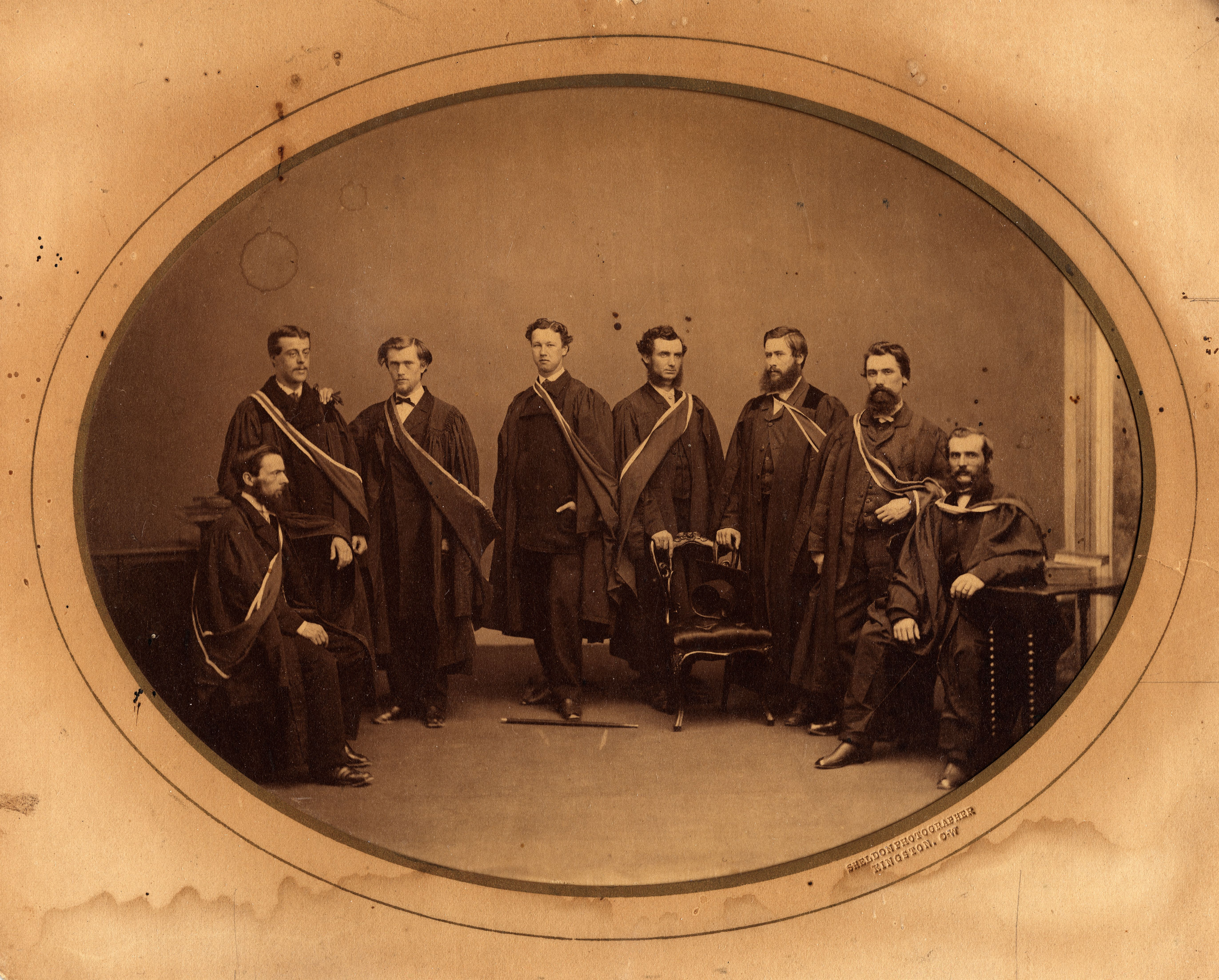 Period photograph of 8 Queen's University medical graduates in academic robes, 1865